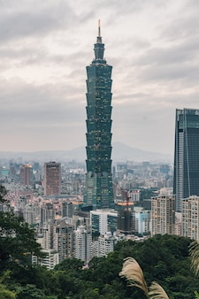 Aerial panorama over downtown taipei with taipei 101 skyscraper with trees on mountain in foreground in the dusk from xiangshan elephant mountain in the evening.