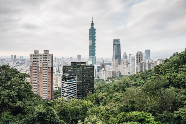 Aerial panorama over downtown taipei with taipei 101 skyscraper with trees on mountain in foreground.