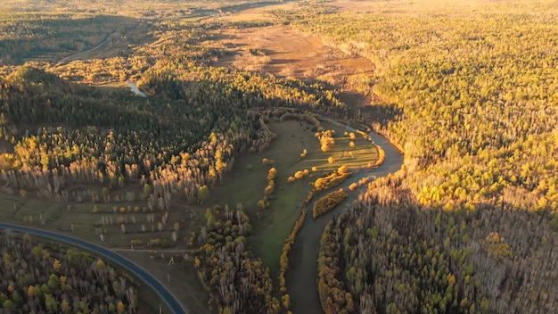 Aerial panorama from drone over a river, fall forest, hill and road. autumn nature rural landscape on sunset from birds eye view.