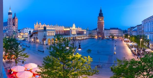 夜、ポーランド、クラクフの旧市街にある織物会館と市庁舎の塔がある中世の中央市場広場の空中パノラマ