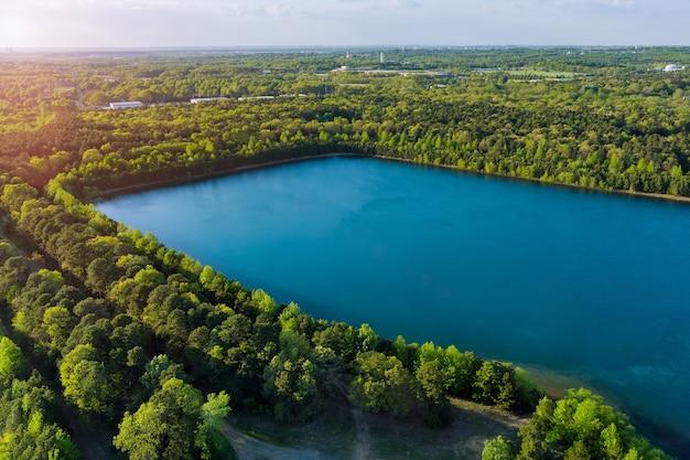 Панорамный вид с воздуха на зеленый лес между бирюзовым озером