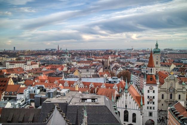Воздушный панорамный городской пейзаж над крышами ретро домов исторической части мюнхена, германия на фоне пасмурного закатного неба.