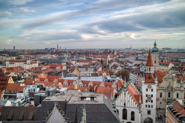 Aerial panoramic townscape above roofs of retro houses historical part of munich, germany on a background of cloudy sunset sky.