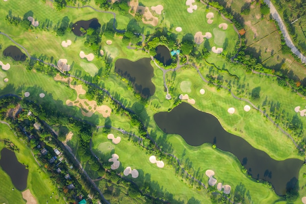 Aerial panoramic view drone shot of beautiful golf course with people playing golf in field.