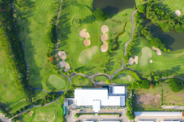 Aerial panoramic view of golf course and houses in city.