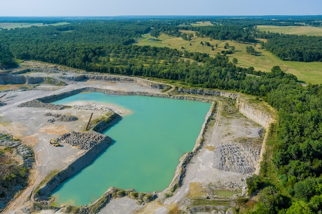 深い緑の湖のある峡谷の露天掘り石抽出の空中パノラマビュー
