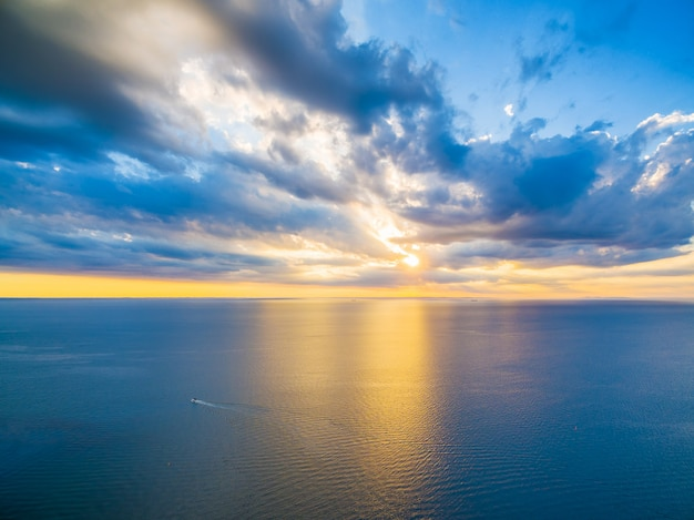 Aerial panoramic view of lonely boat sailing across ocean at beautiful sunset. beautiful glowing yellow light reflecting in blue bay waters.