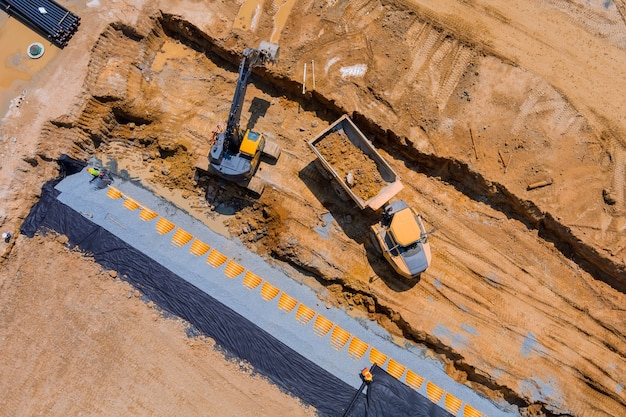 Aerial panoramic view of sewerge construction trench for laying external sewage drainage system construction at earthworks