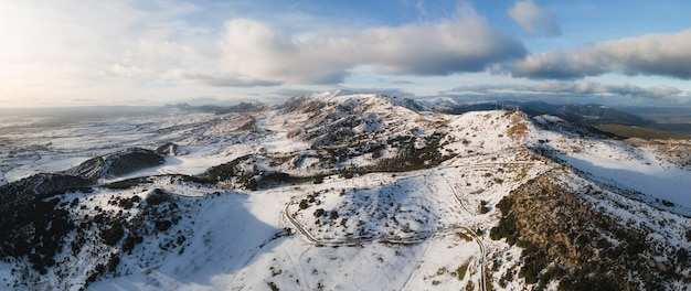 Aerial panoramic view of snow covered high mountains.