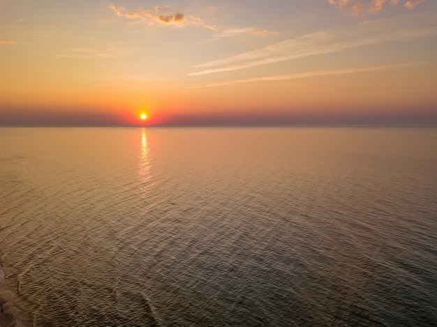 Aerial panoramic view of sunrise over sea. nothing but sky, clouds and water. beautiful serene scene