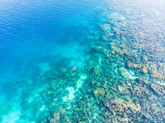 Aerial people snorkeling on coral reef tropical caribbean sea, turquoise water