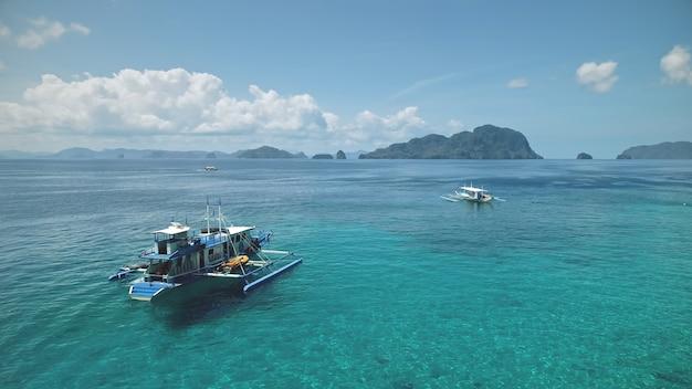 공중 필리핀 바다 만 : 배, 배, 터키석 수면. 관광객을위한 현지 크루즈 투어