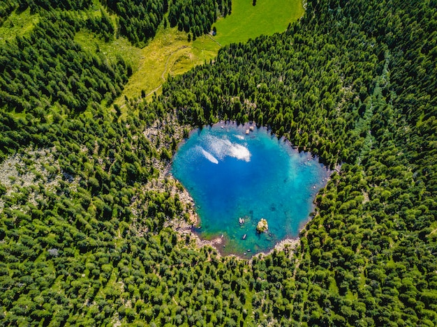 Aerial photo of a blue lake between alpine mountains.