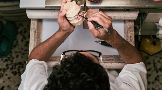 Аэрофотоснимок зубного техника, фиксирующего части зубного протеза с помощью розовой пасты в мастерской