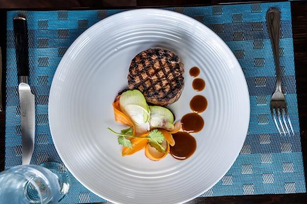 Аэрофотоснимок стейка из филе на гриле с овощами на керамической тарелке, украшенной соусом, с вилками по бокам. коста-рика гастрономия