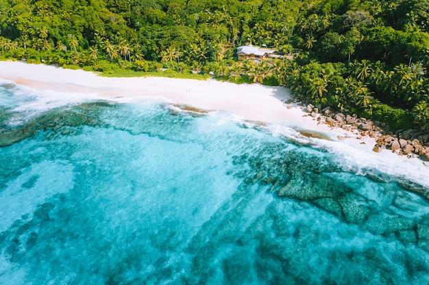 セイシェルのマヘ島にある奇妙な楽園の熱帯のビーチ、アンスバザルカの航空写真。白い砂、ターコイズブルーの水、ヤシの木、花崗岩の岩。