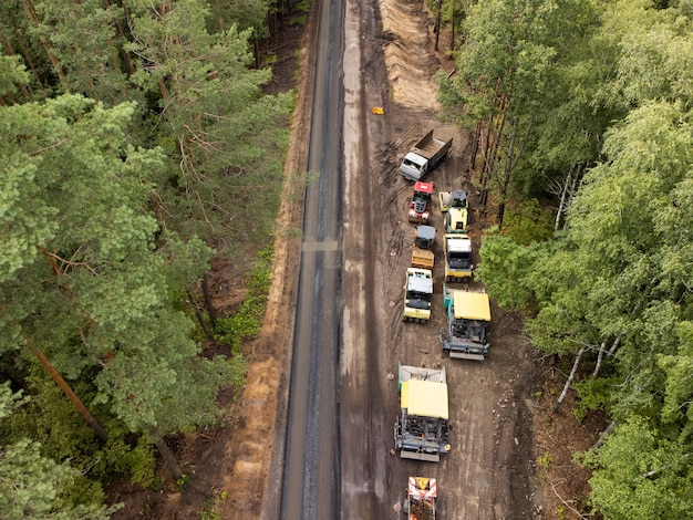 脇道の道路建設機械の航空写真。現代の技術を使用したアスファルト道路の建設と修理