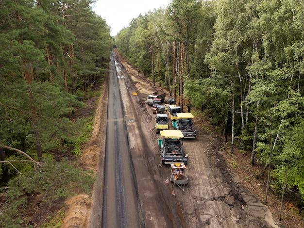 田舎の道路建設工事の航空写真。高品質の近代的なアスファルト舗装を作るための近代的な車両