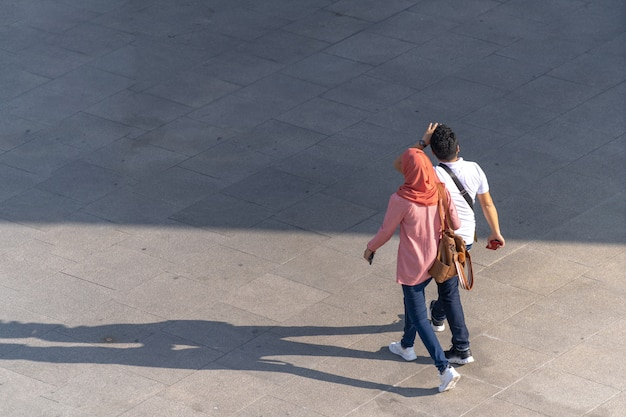 Aerial photo of people walk on the walkway in front of the mall in the city