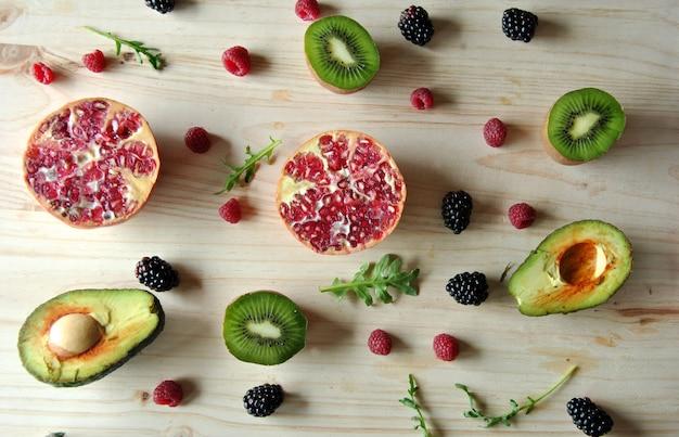 Aerial photo of raspberries, strawberries, avocado and kiwi on wooden background