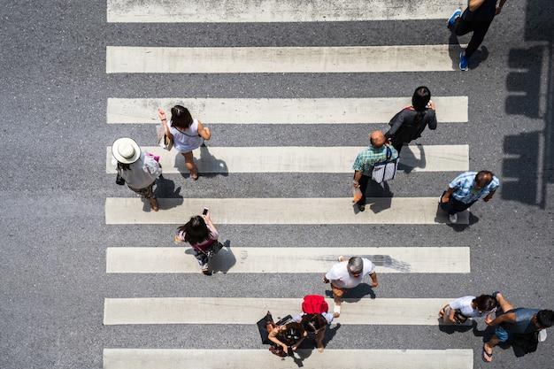 Аэрофотосъемка с высоты птичьего полета людей на улице в городе по пешеходной переправе