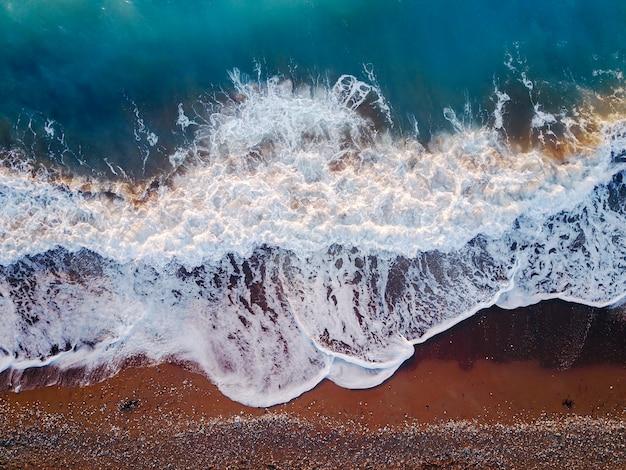 青緑色の水と波と素晴らしいサンゴ海の風景の飛行ドローンからの空中写真ビュー。