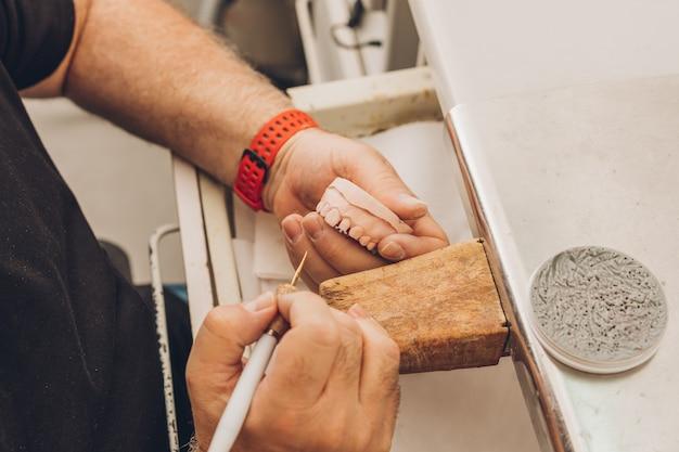 ポーセレンクラウンを作成するための歯科用骨セラミックを専門とする歯科技工所で、ワックスを使用して成形された白人男性の成人の手の拡大図を含む空中写真
