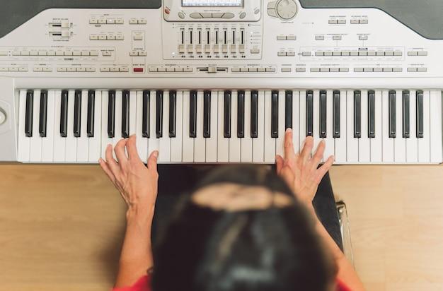 전자 피아노를 연주하는 여성의 손에 선별적으로 초점을 맞춘 항공 사진