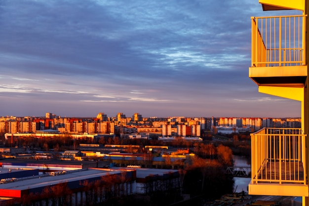 Aerial photography of the evening industrial district of a large russian city with warehouses, warehouses, offices and buildings on the background of balconies. beautiful sky at sunset.