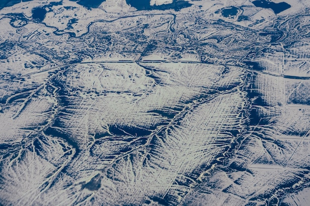 Aerial photography from the height of aircraft mountains in snow in winter in siberia