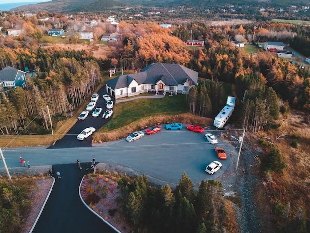 昼間の白い家の前に停まっているクーペの空中写真
