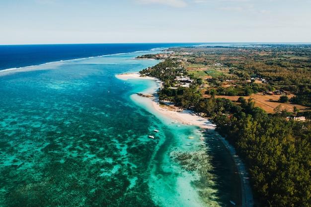 모리셔스 섬 동해안의 항공 사진. belle mare 지역에 있는 모리셔스의 청록색 석호 위로 비행합니다. 모리셔스의 산호초입니다. 모리셔스 섬 해변.