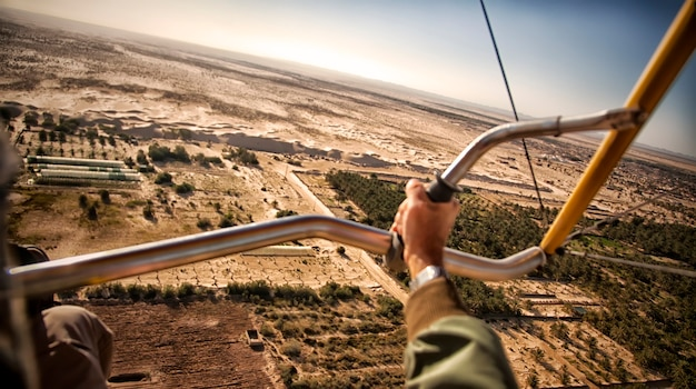 Aerial photography of sand dunes and trees in an oasis in sahara desert. bird's-eye view of hang glider on vast expanses of desert, near city of el jam, tunisia, africa. selective focus