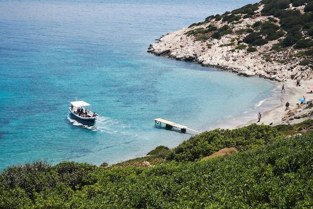アモルゴス島、ギリシャの小さなビーチに近づいているボートの空中写真撮影