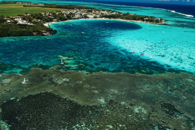 Aerial picture of the east coast of mauritius island. beautiful lagoon of mauritius island shot from above. boat sailing in turquoise lagoon.