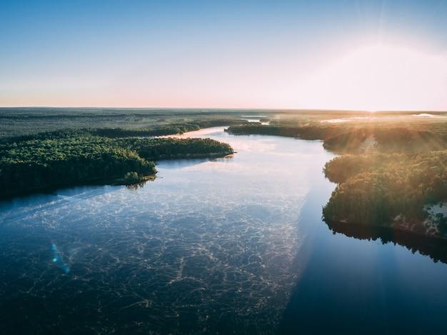 햇빛에 녹지로 덮여 섬으로 둘러싸인 강의 항공 사진