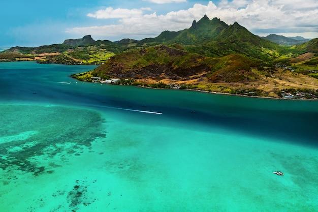 Аэрофотоснимок восточного побережья острова маврикий. красивая лагуна острова маврикий снята сверху. плавание на лодке в бирюзовой лагуне.
