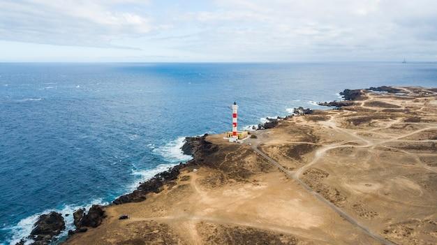 船のために海に光を当てるための海岸の灯台の空中視点。どこにでも行き、砂漠の場所を発見するための多くの道。旅行の冒険の概念