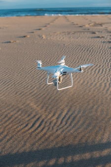 Aerial private drone lands at sand on beach