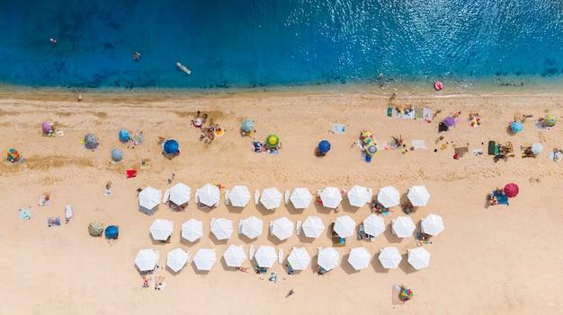 Антенна. песчаный пляж с туристами у моря. вид сверху с дрона.