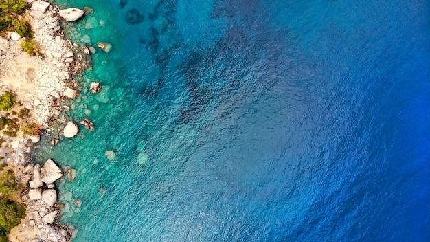 空中。海の水と海岸の岩のテクスチャの背景。ドローンからの上面図。