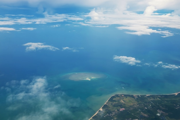 Aerial seascape view from airplane window of  phuket coast and andaman ocean in summer sunny day, thailand. flying along  sea coast through fluffy clouds
