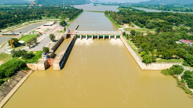 Aerial shooting spring flood water flowing hydroelectric power station dam.