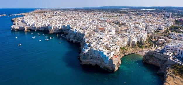 Ripresa aerea del mare adriatico e del paesaggio urbano della città di polignano a mare, puglia, italia meridionale