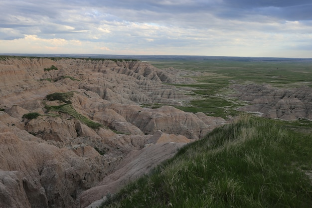 Aerial shot of badlands with grassy fields