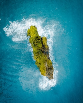 Aerial shot of a beautiful green little island in the middle of the ocean