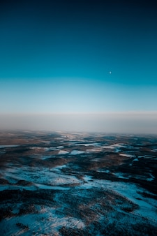 Aerial shot of a beautiful landscape covered with snow in the early morning