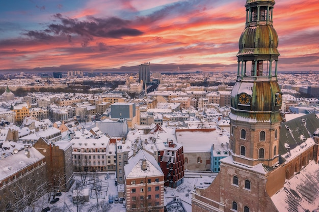 Ripresa aerea del bellissimo tramonto sulla città di riga coperta di neve con il fiume daugava e il centro cittadino