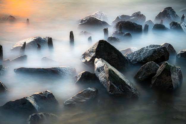 Ripresa aerea di grandi rocce in una spiaggia durante un tempo nebbioso