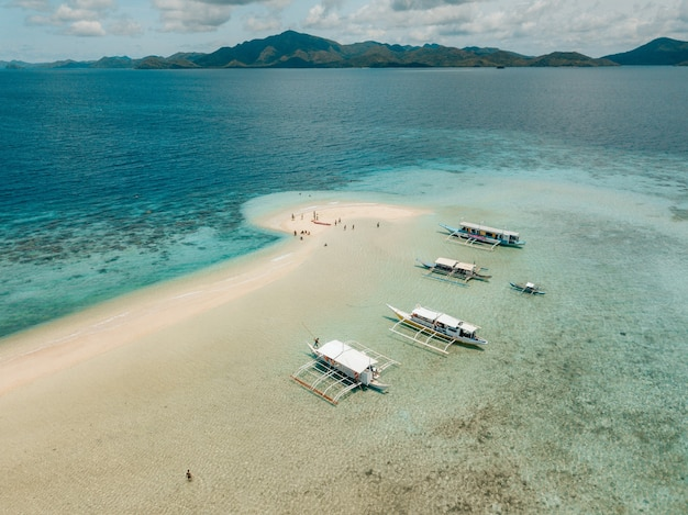 Aerial shot of the boats on the calm crystal clear ocean